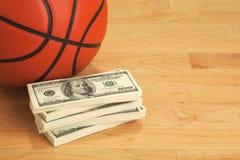 Baloncesto y cientos billetes de dólar en piso de madera de la corte foto de archivo