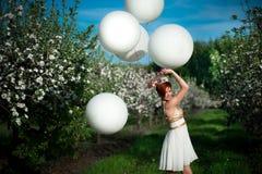 Balones de aire alegres sonrientes de la oferta de la tenencia de la muchacha imagen de archivo libre de regalías