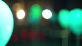 Balones de aire borrosos iluminados con los proyectores coloridos en interior festivo metrajes