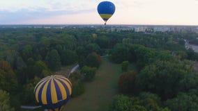 Balones de aire que suben en el cielo sobre la zona verde urbana, campeonato, visión aérea almacen de metraje de vídeo