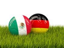 Balones de fútbol de México y de Alemania en hierba Foto de archivo