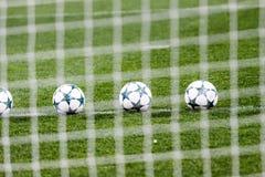 Balones de fútbol en hierba verde Imagen de archivo
