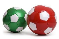 Balones de fútbol rojos y verdes aislados en el fondo blanco Imagen de archivo