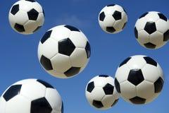Balones de fútbol del fútbol que llueven abajo del cielo Fotografía de archivo