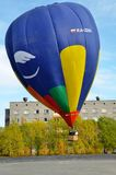 Baloniarze wspinają się balon w niebo na jesieni pogodnym popołudniu obok domów miasteczko Vertical rama Zdjęcia Stock