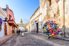Balonowy sprzedawca w ulicie z łukiem, ruinami & volca Santa Catalina, Zdjęcie Stock