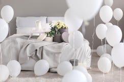 Balony w przemysłowej eleganckiej sypialni z popielatymi pościeli, trey i round pudełkami z kwiatami na th łóżku, zdjęcia royalty free