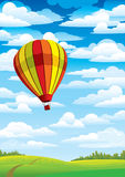 Baloon. Colored balloon on a blue sky, white clouds and green meadow Royalty Free Stock Images