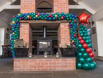 Baloon arche above fireplace with christmas tree made from baloons. Baloon arche and christmas tree next to pub`s fireplace in Birmingham, United Kingdom made by stock photo