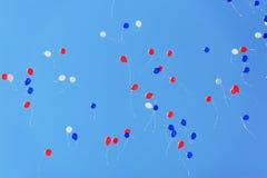 Baloons blancs, bleus et rouges volant haut en ciel bleu clair Photographie stock libre de droits