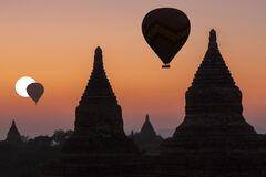 Baloons and Buddhist temples in silhouette over Bagan, Myanmar