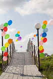 Baloons coloridos del helio en el puente enfrente del cielo azul Foto de archivo