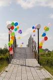 Baloons coloridos del helio en el puente enfrente del cielo azul Foto de archivo libre de regalías