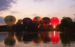 Baloons d'air chaud volant dans le ciel de soirée près du lac Photos stock