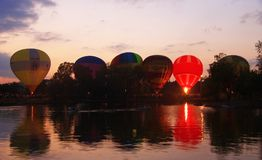 Baloons d'air chaud volant dans le ciel de soirée près du lac Photographie stock