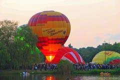 Baloons d'air chaud volant dans le ciel de soirée près du lac Images stock