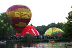 Baloons d'air chaud volant dans le ciel de soirée près du lac Image stock