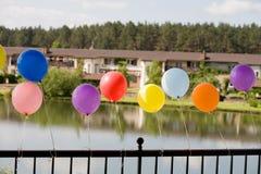Baloons del helio en el puente con el lago y las casas   Fotos de archivo libres de regalías