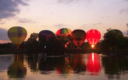 Baloons dell'aria calda che volano nel cielo di sera vicino al lago Fotografie Stock