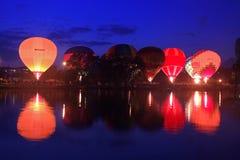 Baloons dell'aria calda che volano nel cielo di sera vicino al lago Immagini Stock Libere da Diritti