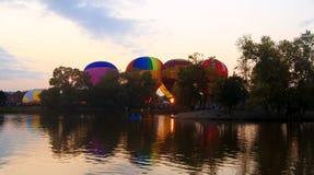 Baloons dell'aria calda che volano nel cielo di sera vicino al lago Immagine Stock Libera da Diritti