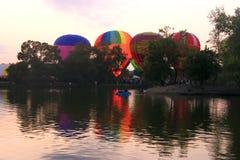Baloons do ar quente que voam no céu da noite perto do lago Imagens de Stock Royalty Free
