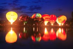 Baloons do ar quente que voam no céu da noite perto do lago Foto de Stock Royalty Free