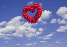 Baloons en forma de corazón en el cielo Fotos de archivo