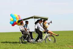Baloons woman leading 4 guys on a quad bike on a green field sunny day Royalty Free Stock Photography