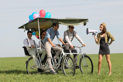 Baloons woman leading 4 guys on a quad bike on a green field sunny day Stock Image