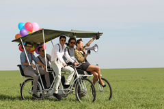 Baloons woman leading 4 guys on a quad bike on a green field sunny day Stock Photos