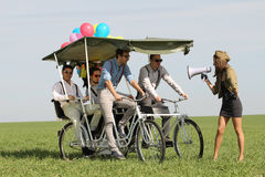 Baloons woman leading 4 guys on a quad bike on a green field sunny day Royalty Free Stock Images