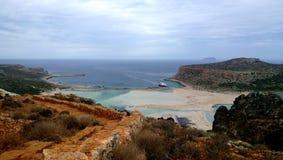 Balos著名海湾的惊人的明亮的看法在克利特 在前景、海和船的被毁坏的明亮的棕色墙壁在 库存照片