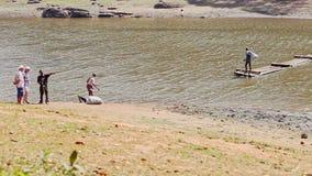 Balsa de Guy Returns Back Large Wooden del indio al otro banco del lago almacen de video