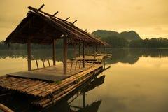 Balsa de madera en el agua antes de la salida del sol Imagen de archivo