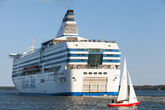 A balsa de Silja Line e o veleiro pequeno navegam do porto de Helsínquia Imagens de Stock