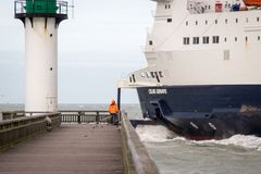 Balsa dos mares de Calais que sai do porto de Calais As capturas do pescador pescam do cais no farol fotos de stock royalty free