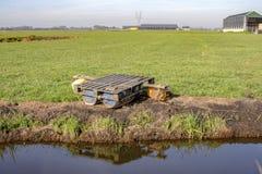 Balsa hecha en casa con los flotadores plásticos, plataforma y cuerda, reflexión en una cala y una granja en el horizonte imagen de archivo