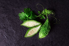 Balsam Pear on wet black stone plate background Stock Image