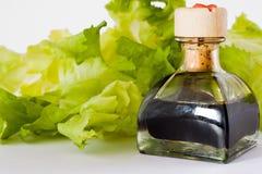 Balsamic vinegar. Little bottle of balsamic vinegar with green salad royalty free stock photo