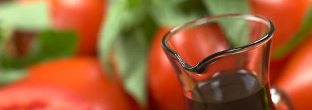 Balsamic Vinegar. With tomato and basil in the back (Very Shallow Depth of Field, Focus on the front of the bottle rim stock photos