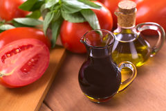 Balsamic Vinegar. With olive oil, tomato and basil in the background (Selective Focus, Focus on the front of the rim of the vinegar bottle royalty free stock image