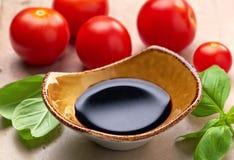 Balsamic vinegar. Bowl of Balsamic vinegar and basil leaves stock photos