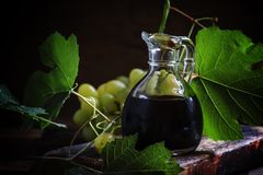 Balsamic vinegar in a glass jug, vintage wooden background, rust. Ic style, selective focus stock images