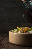 Balsamic vinegar pours from glass jug into a salad in a wooden d Royalty Free Stock Photo
