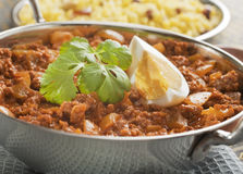 Balti Keema Curry and Rice. Indian curry, beef keema with egg, in a balti dish, garnished with coriander, with rice pilau Stock Photos