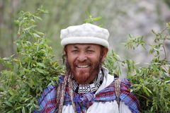 Balti man in traditional dress is carrying willow twigs and branches