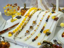 Baltic amber jewelry bracelets on a white stand on the showcase of a jewelry store. Amber in silver bracelets and rings stock photo