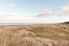 Baltic beach in fall with clouds and waves towards deserted dune Royalty Free Stock Photos