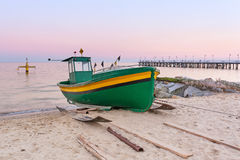 Baltic beach with fishing boat at sunset Stock Photo